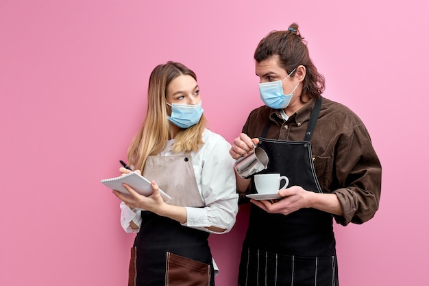 Two young waiters in apron and mask discuss orders, ready to serve clients during quarantine