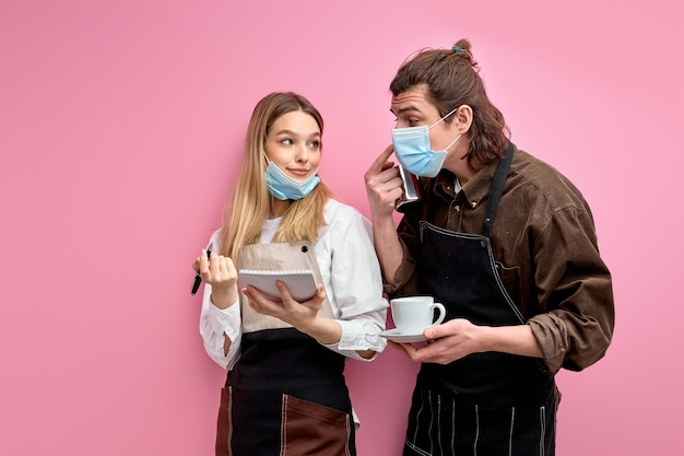 Два молодых официанта в фартуке и маске обсуждают заказы, готовы обслуживать клиентов во время карантина