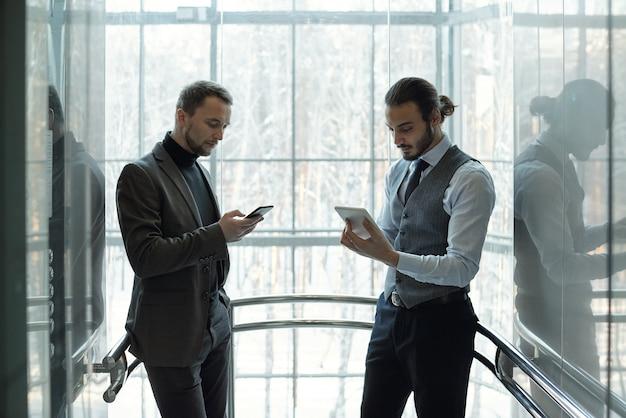 Два молодых хорошо одетых бизнесмена с помощью мобильных гаджетов во время перерыва, стоя у окна современного бизнес-центра