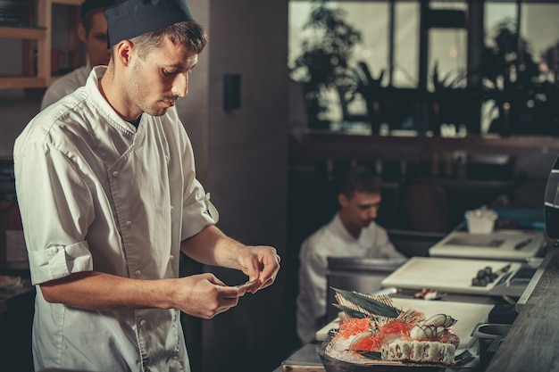 흰색 제복을 입은 두 젊은 백인 요리사가 작업 중인 레스토랑에서 준비된 요리를 장식합니다
