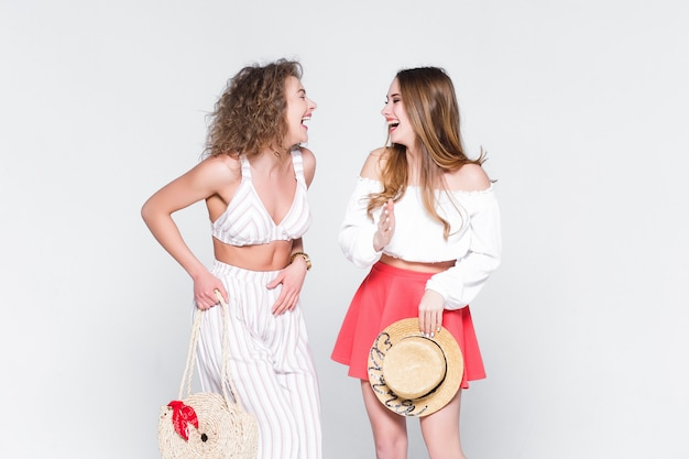 Two young woman bloggers talk about travel live, on white .