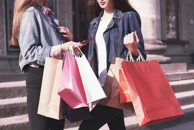 店を訪れた後、通りを歩きながら買い物袋を運ぶ2人の若い女性。