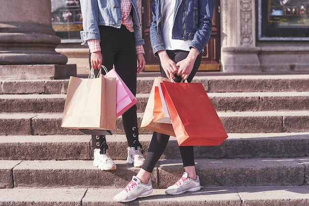 Две молодые женщины, несущие хозяйственные сумки во время прогулки по лестнице после посещения магазинов.