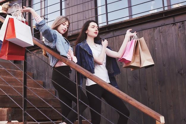 店を訪れた後、階段を歩きながら買い物袋を運ぶ2人の若い女性。