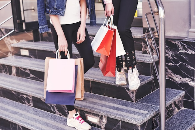 Two young woman carrying shopping bags while walking on the stairs after visiting the stores.