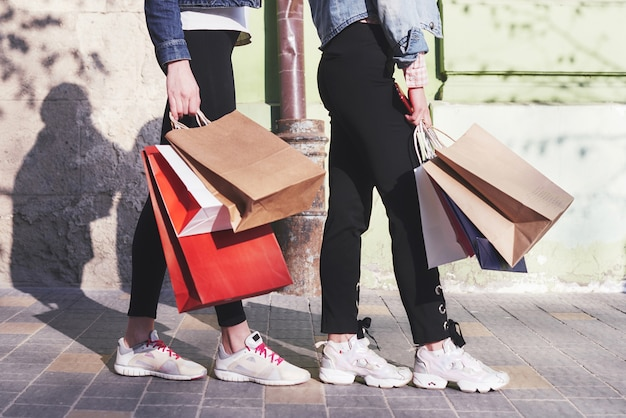 Two young woman carrying shopping bags while walking in the street after visiting the stores.