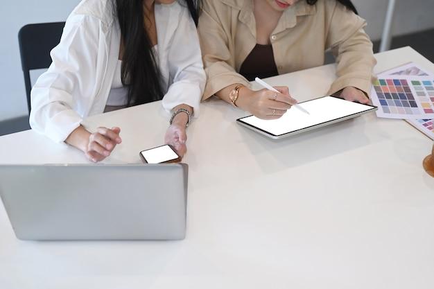 Два молодых дизайнера женщины говорят о новых идеях и работают на планшете компьютера.
