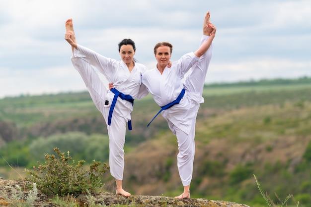Two young woman doing synchronised acro yoga or acrobatic yoga balancing