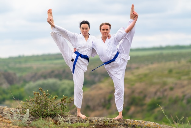Two young woman doing a synchronised workout routine outdoors