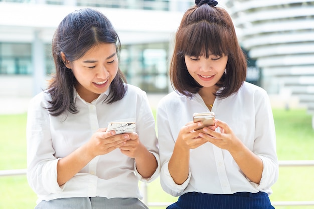 Two young woman enjoy using their smart phone to connect to digital social media