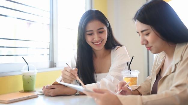 현대 카페에서 디지털 태블릿으로 함께 일하는 두 젊은 여성 기업가.
