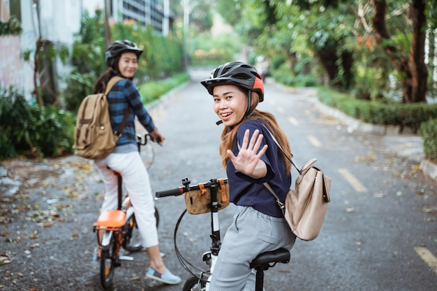 Two young woman is ready to go by folding bike and looks back with high five