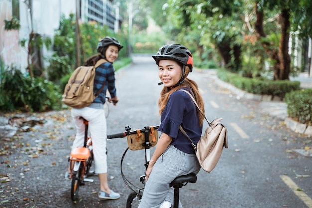 Two young woman is ready to go by folding bike