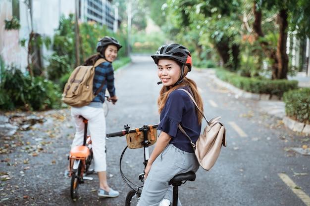 2人の若い女性は折りたたみ自転車で行く準備ができています