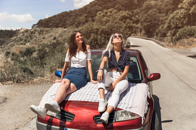 Two young woman sitting on car relaxing