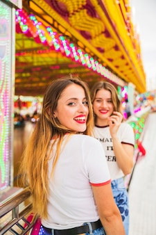 Two young woman standing in front of amusement park