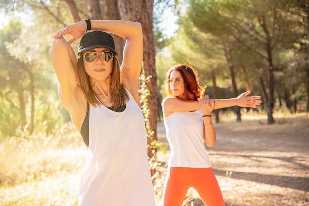 두 젊은 여성이 다리와 몸을 쭉 뻗고 숲에서 야외 조깅을 한 후 휴식을 취합니다