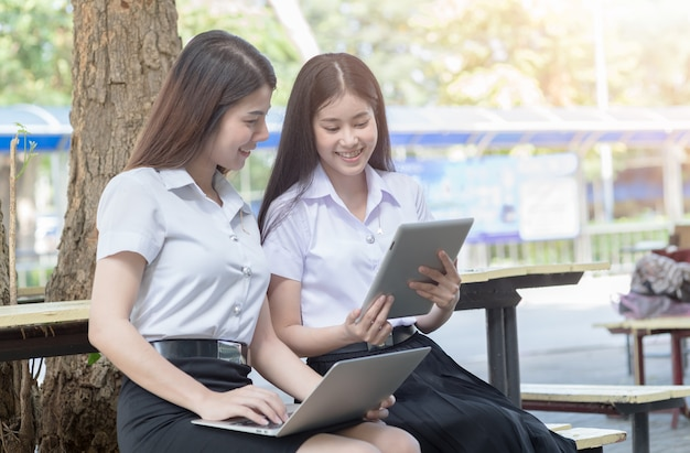 Two young woman student play tablet and laptop on chair in university, education concept