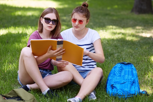 Two young woman study together in park, wears casual clothes and sunglasses, read abstracts while preparing for seminar in university, have concentrated facial expressions. students and education