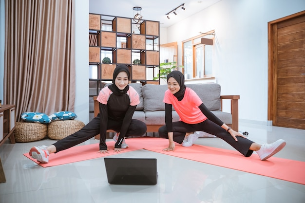 Two young woman wearing a hijab gym clothes squatting stretches with one leg pulled sideways while in front of a laptop in the house