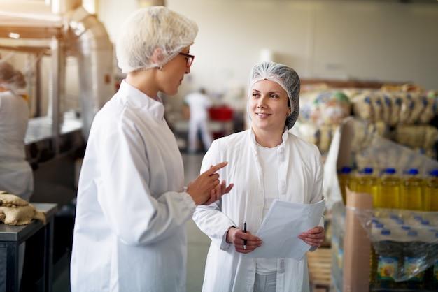 Две молодые женщины, работающие в стерильной одежде, проводят мозговой штурм, как улучшить статистические отношения в пищевой промышленности при проведении работ.