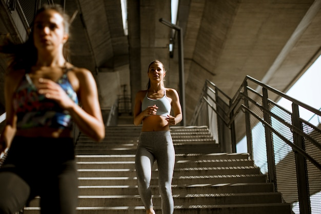 Two young woman workout in urban environment