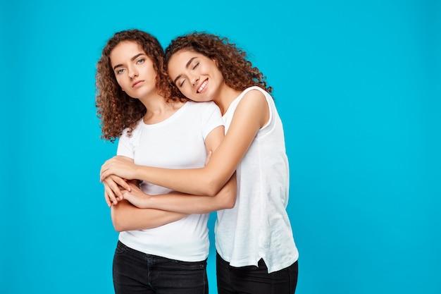 2つの若い梨花双子を受け入れ、青に笑みを浮かべてします。