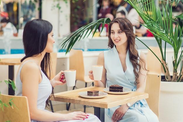 2人の若い女性が屋外のカフェでケーキとコーヒーを飲んでいます。