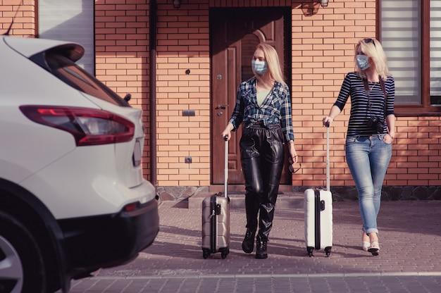 Две молодые женщины собираются путешествовать на машине