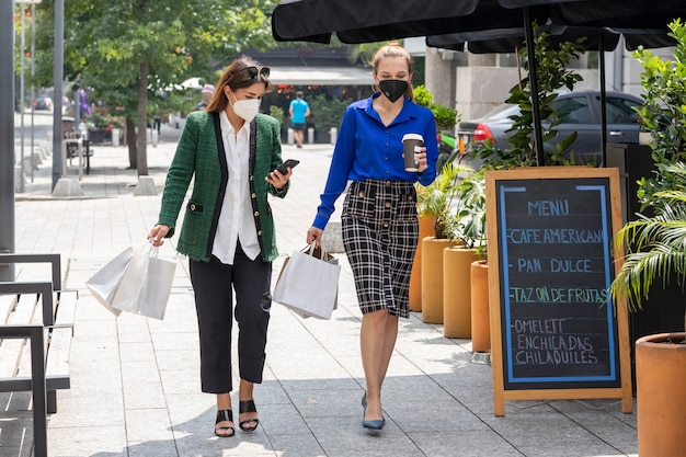 Две молодые женщины идут по улице в масках и радостно разговаривают после покупок