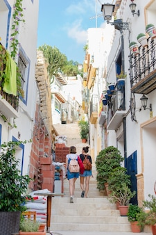 Two young women are walking on the street in alicante, spain