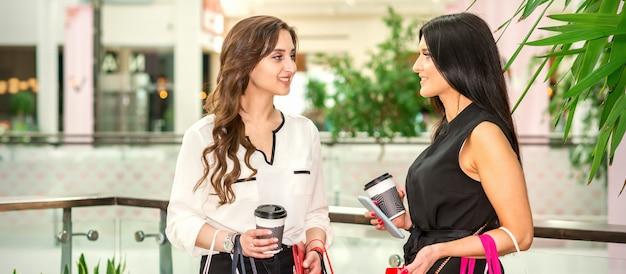 Две молодые женщины в торговом центре