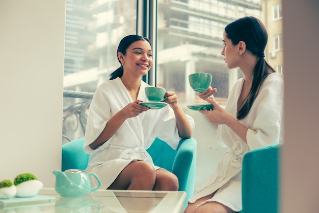 Two young women in bathrobes having an interesting conversation while sitting in armchairs and drinking tea