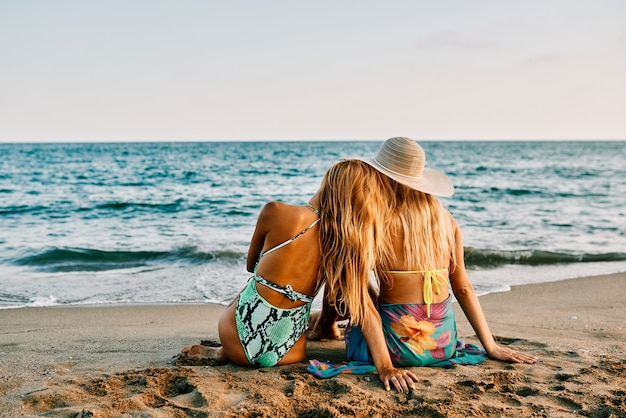 Two young women at the beach at sunset - summer concept