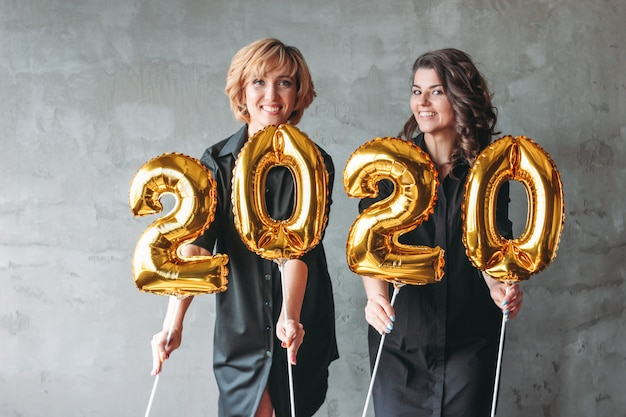 Two young women in black dresses holding 2020 numbers balloons on the grey wall background