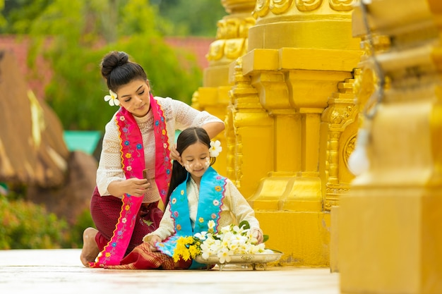 Two young women in burmese national costumes are helping to arrange flowers when offering to monks on important buddhist dates.