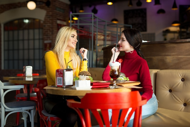 Две молодые женщины болтают в кафе