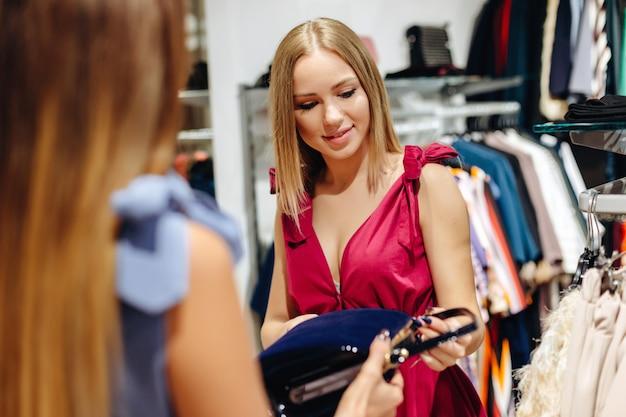 Two young women choosing bag in a showroom