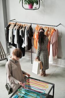 Две молодые женщины выбирают новую одежду и аксессуары в торговом центре