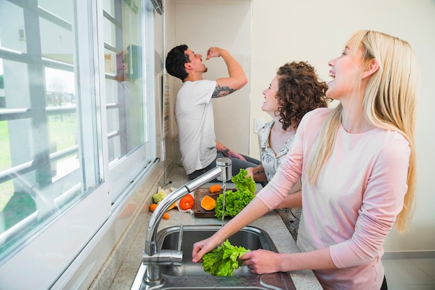 Two young women cleaning the lettuce vegetable laughing while looking at man eating carrot