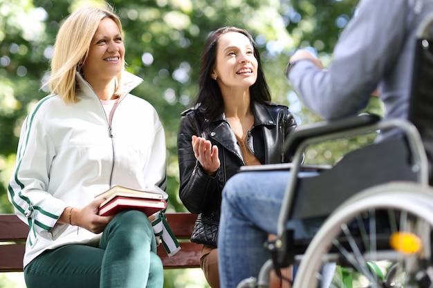 두 젊은 여성이 공원에서 휠체어를 탄 남자와 의사소통을 합니다.