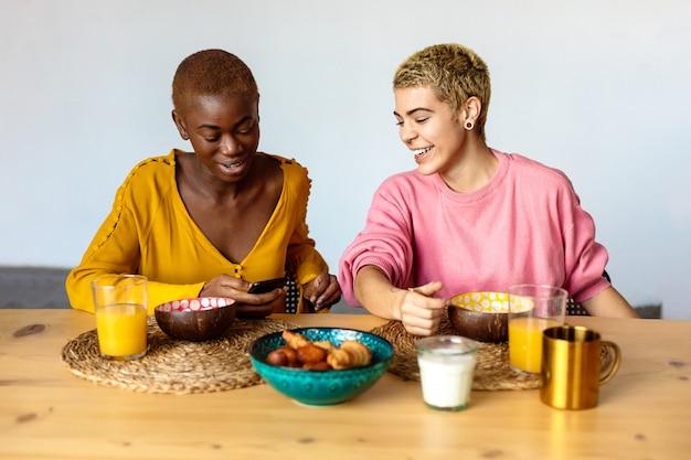 두 젊은 여성 커플, 카페에 앉아 가장 친한 친구, 아침 식사와 커피를 마시고, 스마트 폰을 사용합니다.