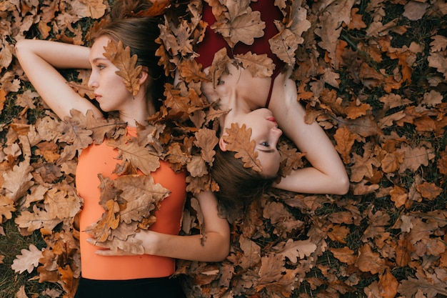 Two young women covered with  autumn leaves while lying on ground and looking at different directions.