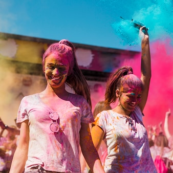 Two young women covered with holi color dancing in the holi festival