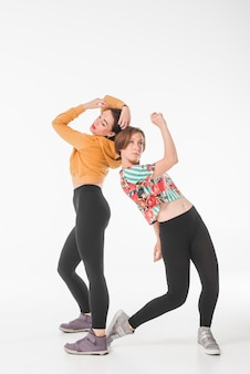 Two young women dancing in front of white background