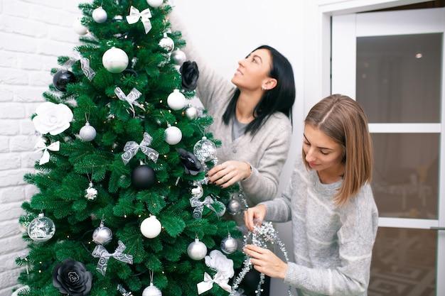 크리스마스 트리를 장식하는 두 젊은 여성