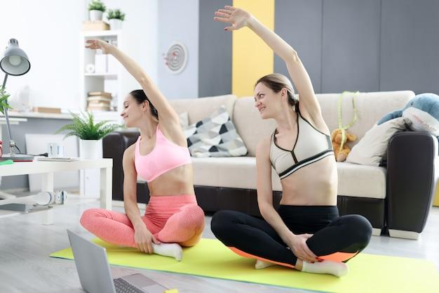 Две молодые женщины занимаются фитнесом перед ноутбуком дома. концепция спортивного онлайн-обучения