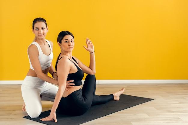 Две молодые женщины делают скручивание в фитнес-йоге