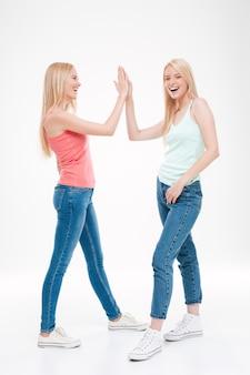 Tシャツとジーンズに身を包んだ2人の若い女性がハイタッチをしました。白い壁に隔離。