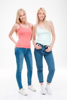 Tシャツとジーンズのポーズを着た2人の若い女性。白い壁に隔離。正面を見てください。